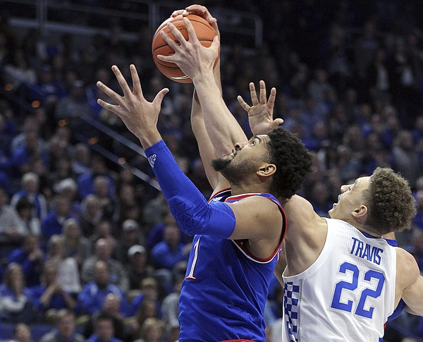 Kansas' Dedric Lawson, left, and Kentucky's Reid Travis (22) compete for a rebound during the first half of an NCAA college basketball game in Lexington, Ky., Saturday, Jan. 26, 2019.