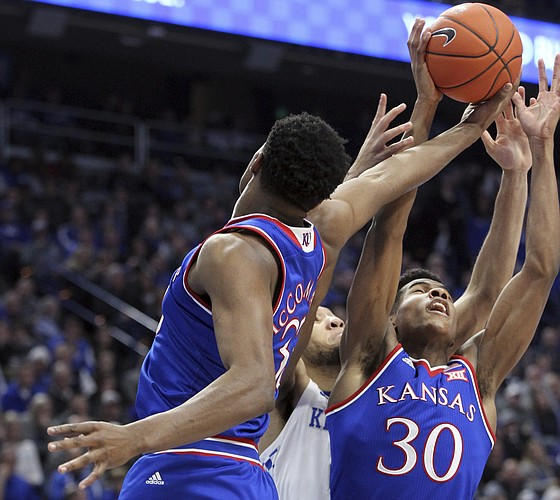 Kansas' Ochai Agbaji (30) and teammate David McCormack, left, battle for a rebound with Kentucky's EJ Montgomery during the first half of an NCAA college basketball game in Lexington, Ky., Saturday, Jan. 26, 2019.