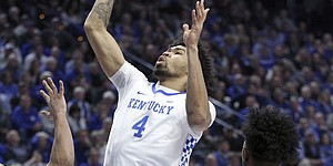 Kentucky's Nick Richards (4) shoots between Kansas' Quentin Grimes, left, and Marcus Garrett (0) during the first half of an NCAA college basketball game in Lexington, Ky., Saturday, Jan. 26, 2019.