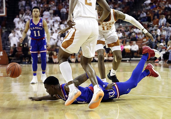 Kansas guard Lagerald Vick (24) falls to the floor past Texas guard Kerwin Roach II (12) and guard Matt Coleman III (2) as he loses control of the ball during the first half on an NCAA college basketball game in Austin, Texas, Tuesday, Jan. 29, 2019. (AP Photo/Eric Gay)