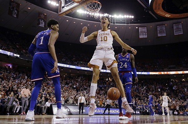 Texas forward Jaxson Hayes (10) celebrates after he scored between Kansas forward Dedric Lawson (1) and guard Lagerald Vick (24) during the second half on an NCAA college basketball game in Austin, Texas, Tuesday, Jan. 29, 2019. Texas won 73-63. (AP Photo/Eric Gay)