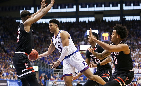 Kansas guard Quentin Grimes (5) gets around Texas Tech forward Khavon Moore (21) to throw a pass in the paint during the second half, Saturday, Feb. 2, 2019 at Allen Fieldhouse.