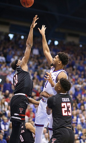 Kansas forward Dedric Lawson (1) puts up a shot over Texas Tech forward Tariq Owens (11) and Texas Tech guard Jarrett Culver (23) during the first half, Saturday, Feb. 2, 2019 at Allen Fieldhouse.