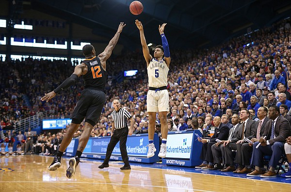 Kansas guard Quentin Grimes (5) puts up a three over Oklahoma State forward Cameron McGriff (12) during the second half, Saturday, Feb. 9, 2019 at Allen Fieldhouse.