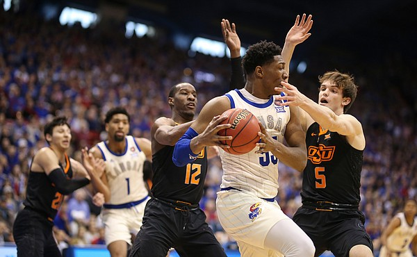 Kansas forward David McCormack (33) is hounded by Oklahoma State forward Duncan Demuth (5) and Oklahoma State forward Cameron McGriff (12) during the first half, Saturday, Feb. 9, 2019 at Allen Fieldhouse.