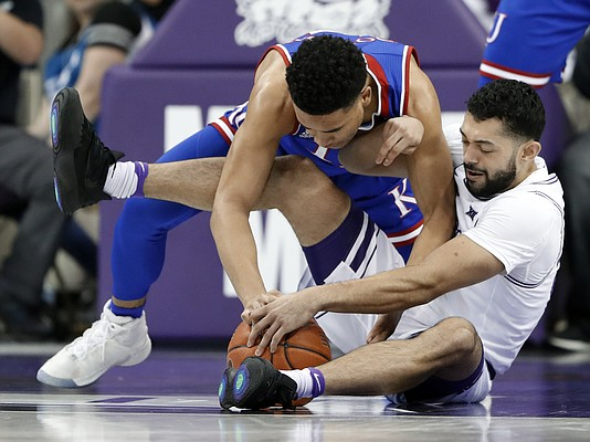 Kansas guard Devon Dotson, top, and TCU guard Alex Robinson, bottom, wrestle for control of a loose ball in the first half of an NCAA college basketball game in Fort Worth, Texas, Monday, Feb. 11, 2019. (AP Photo/Tony Gutierrez)