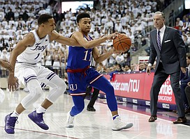 TCU guard Desmond Bane (1) attempts to strip the ball away from Kansas guard Devon Dotson (11) as TCU head coach Jamie Dixon, right, watches in the first half of an NCAA college basketball game in Fort Worth, Texas, Monday, Feb. 11, 2019. (AP Photo/Tony Gutierrez)