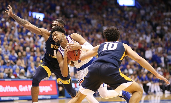 Kansas forward Dedric Lawson (1) drives to the bucket between West Virginia forward Derek Culver (1) and West Virginia guard Jermaine Haley (10) during the first half, Saturday, Feb. 16, 2019 at Allen Fieldhouse.