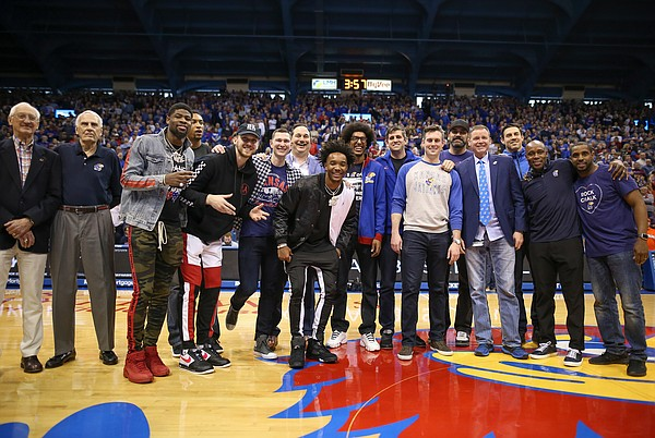 A host of former Jayhawk players come together for a photo after being introduced at half court during halftime, Saturday, Feb. 16, 2019 at Allen Fieldhouse.