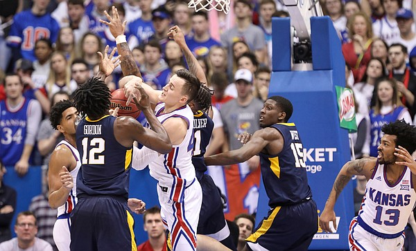 Kansas forward Mitch Lightfoot (44) battles in the paint for a ball with West Virginia forward Andrew Gordon (12) during the first half, Saturday, Feb. 16, 2019 at Allen Fieldhouse.