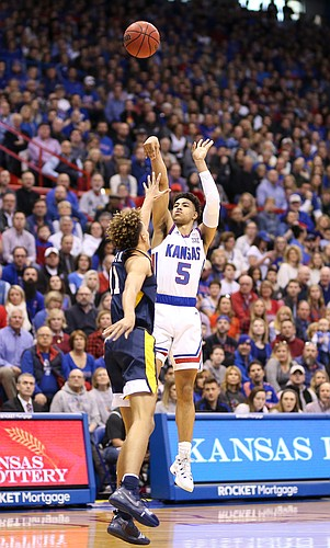 Kansas guard Quentin Grimes (5) puts up a three over West Virginia forward Emmitt Matthews Jr. (11) during the first half, Saturday, Feb. 16, 2019 at Allen Fieldhouse.