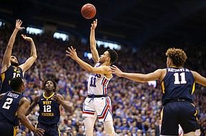 Kansas guard Devon Dotson (11) floats a shot over the West Virginia defense during the first half, Saturday, Feb. 16, 2019 at Allen Fieldhouse.