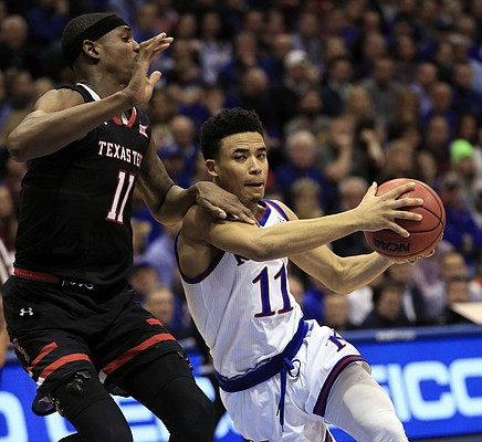 Kansas guard Devon Dotson, right, drives on Texas Tech forward Tariq Owens, left, during the first half of an NCAA college basketball game in Lawrence, Kan., Saturday, Feb. 2, 2019. (AP Photo/Orlin Wagner)
