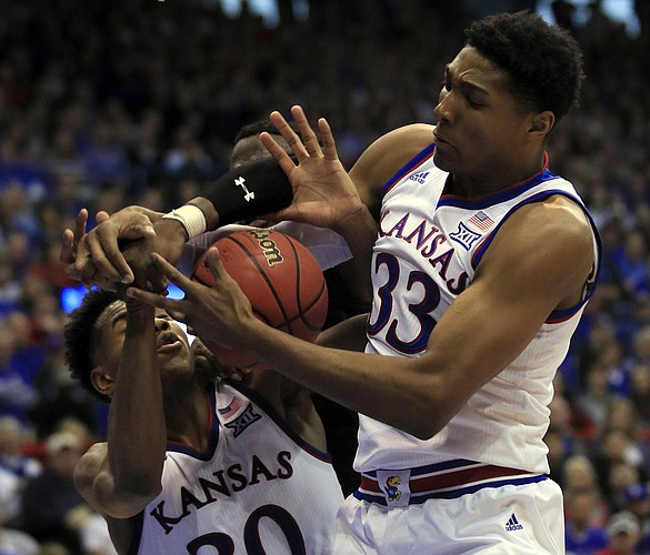Kansas forward David McCormack (33) rebounds with guard Ochai Agbaji (30) during the second half of an NCAA college basketball game in Lawrence, Kan., Saturday, Feb. 2, 2019. Texas Tech center Norense Odiase, back, is boxed out on the play. Kansas defeated Texas Tech 79-63. (AP Photo/Orlin Wagner)