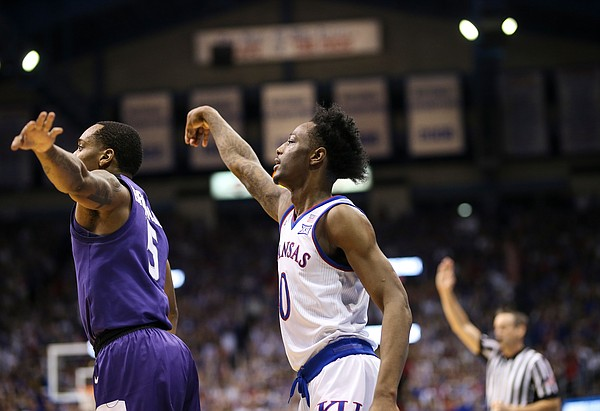 Kansas guard Marcus Garrett (0) watches his three pointer behind Kansas State guard Barry Brown Jr. (5) during the first half, Monday, Feb. 25, 2019 at Allen Fieldhouse.