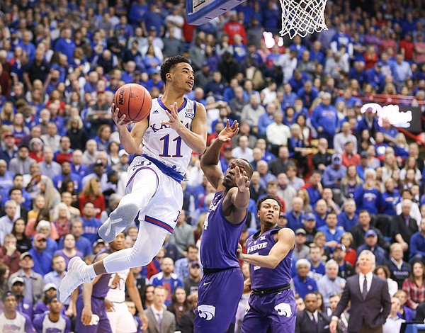 Kansas guard Devon Dotson (11) looks for an outlet past as he soars past Kansas State forward Makol Mawien (14) during the first half, Monday, Feb. 25, 2019 at Allen Fieldhouse.
