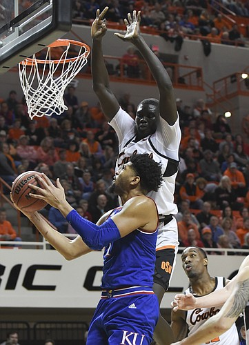 Oklahoma State forward Cameron McGriff, right, watches as Kansas guard Dedric Lawson, left, takes as shot under pressure from Oklahoma State forward Yor Anei during an NCAA college basketball game in Stillwater, Okla., Saturday, March 3, 2019. Lawson led scoring for Kansas with 20 points in the 72-67 win over Oklahoma State. (AP Photo/Brody Schmidt)