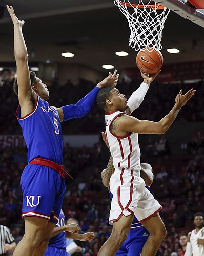 Oklahoma guard Miles Reynolds, right, tries to score in front of Kansas guard Quentin Grimes, left, in the second half of an NCAA college basketball game in Norman, Okla., Tuesday, March 5, 2019. Oklahoma won 81-68. (AP Photo/Nate Billings)