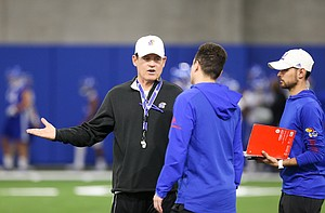 Kansas head coach Les Miles talks with members of his staff during football practice on Wednesday, March 6, 2019 within the new indoor practice facility.