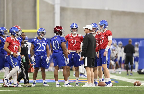 Kansas head coach Les Miles talks with quarterbacks and running backs during football practice on Wednesday, March 6, 2019 within the new indoor practice facility.
