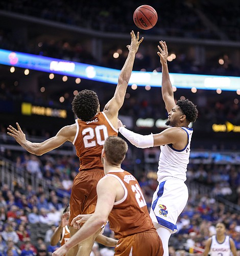 Kansas forward Dedric Lawson (1) turns around for a shot over Texas forward Jericho Sims (20) during the second half, Thursday, March 14, 2019 at Sprint Center in Kansas City, Mo.