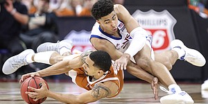 Kansas guard Quentin Grimes (5) and Texas guard Elijah Mitrou-Long (55) dive for a ball during the second half, Thursday, March 14, 2019 at Sprint Center in Kansas City, Mo.