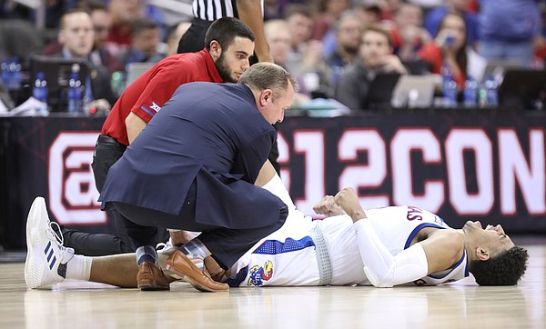 Kansas guard Quentin Grimes (5) is visited by trainers as he lies on the floor with a cramp during the second half, Friday, March 15, 2019 at Sprint Center in Kansas City, Mo.