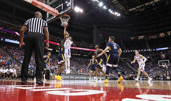 Kansas forward Dedric Lawson (1) turns for a shot over West Virginia forward Lamont West (15) during the first half, Friday, March 15, 2019 at Sprint Center in Kansas City, Mo.