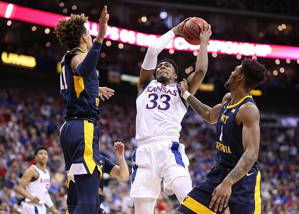 Kansas forward David McCormack (33) pulls a rebound from West Virginia forward Emmitt Matthews Jr. (11) and West Virginia forward Derek Culver (1) during the first half, Friday, March 15, 2019 at Sprint Center in Kansas City, Mo.