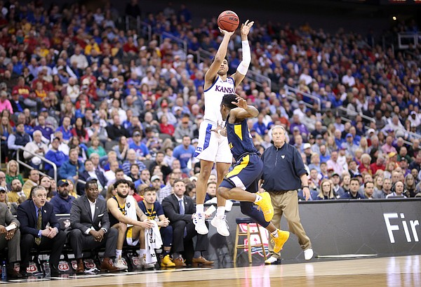 Kansas guard Quentin Grimes (5) puts up a three-pointer as he is fouled by West Virginia guard Brandon Knapper (2) during the first half, Friday, March 15, 2019 at Sprint Center in Kansas City, Mo.