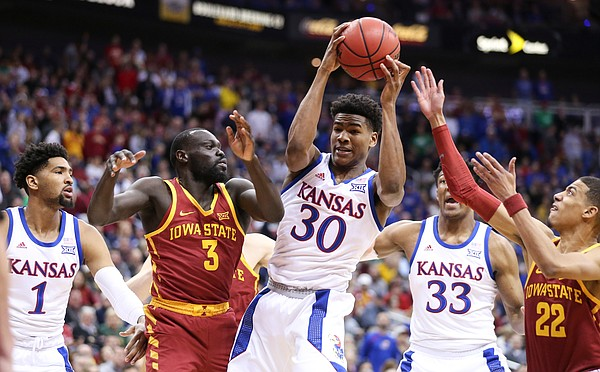 Kansas guard Ochai Agbaji (30) grabs a rebound between Iowa State guard Marial Shayok (3) and Iowa State guard Tyrese Haliburton (22) during the first half, Saturday, March 16, 2019 at Sprint Center in Kansas City, Mo.
