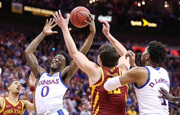 Kansas guard Marcus Garrett (0) grabs an offensive rebound from Iowa State forward Michael Jacobson (12) during the first half, Saturday, March 16, 2019 at Sprint Center in Kansas City, Mo.