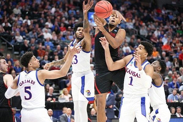 Kansas guard Quentin Grimes (5), Kansas guard K.J. Lawson (13), Kansas forward Dedric Lawson (1) and Kansas guard Marcus Garrett (0) fight for a loose ball with Northeastern center Anthony Green (30) during the first half, Thursday, March 21, 2019 at Vivint Smart Homes Arena in Salt Lake City, Utah.