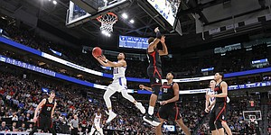Kansas guard Devon Dotson (11) gets under the Northeastern defense for a bucket during the first half, Thursday, March 21, 2019 at Vivint Smart Homes Arena in Salt Lake City, Utah.