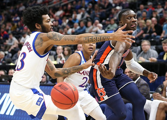 Auburn guard Jared Harper (1) hooks a pass around Kansas guard K.J. Lawson (13) and Kansas guard Charlie Moore (2) late in the second half on Saturday, March 23, 2019 at Vivint Smart Homes Arena in Salt Lake City, Utah.
