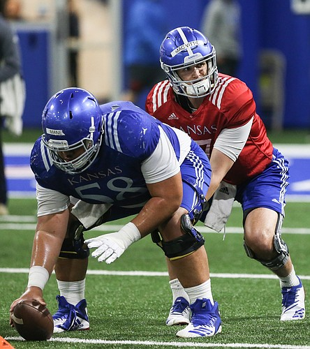 Kansas quarterback Thomas MacVittie looks to take a snap from offensive lineman Api Mane on Thursday, April 4, 2019 at the indoor practice facility.