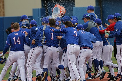 Kansas redshirt-freshman Dylan Ditzenberger is showered with water after hitting the game winning single in the bottom of the ninth against Oklahoma State at Hoglund Ballpark, April 13, 2019.