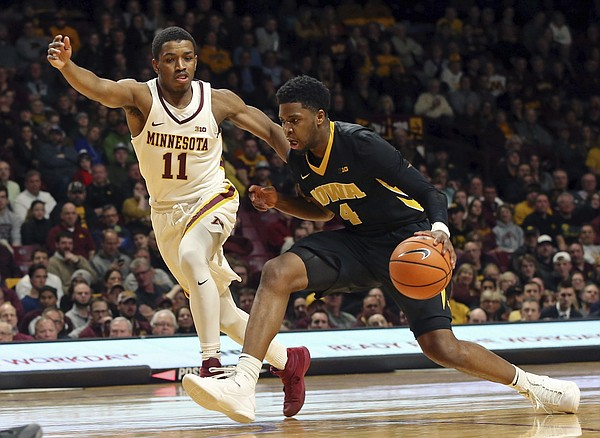 Iowa's Isaiah Moss, right, drives as Minnesota's Isaiah Washington gives chase in the first half of an NCAA college basketball game Wednesday, Feb. 21, 2018, in Minneapolis. (AP Photo/Jim Mone)