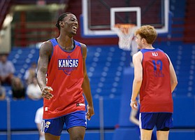Kansas guard Marcus Garrett (0) has a laugh after an attempted dunk by Kansas forward Mitch Lightfoot went off the back iron during a scrimmage on Tuesday, June 11, 2019 at Allen Fieldhouse.