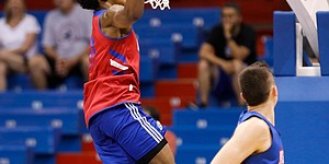 Kansas guard Ochai Agbaji delivers a dunk past Kansas forward Mitch Lightfoot during a scrimmage on Tuesday, June 18, 2019 at Allen Fieldhouse.