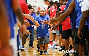 """Eleven-year-old Sergio Gomez, a member of the Rock Chalk Roundball Classic """"Starting Five"""" greets the players before tipoff on Thursday, June 20, 2019 at Eudora High School."""