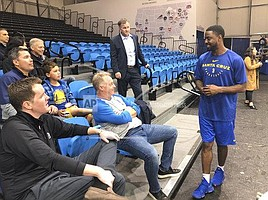 In this Dec. 4, 2018 photo, from left, Santa Cruz Warriors coach Aaron Miles visits with fans and sponsors after their basketball practice in Santa Cruz, Calif. As the Santa Cruz Warriors huddled together after practice, Darius Morris gave a quick recap of his adventure to the Arizona desert a day earlier to interview with the Suns. Phoenix needed a point guard with Devin Booker's hamstring injury, and Morris was in the mix. Coach Aaron Miles, who so wishes he were still playing, had to stand in leading the offense given Morris' absence. Such is life in the topsy-turvy, changing-by-the-day G League, when Golden State or another club might come calling at a moment's notice to swipe a top player for promotion to the NBA. (AP Photo/Janie McCauley)