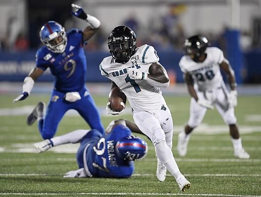 Coastal Carolina running back CJ Marable gets past two Kansas defenders Saturday night at David Booth Kansas Memorial Stadium on Sept. 7, 2019.