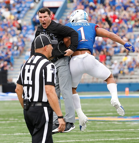 Kansas safety Bryce Torneden (1) and special teams coach Mike Ekeler get airborne as they celebrate a missed field goal by the Mountaineers during the second quarter on Saturday, Sept. 21, 2019 at David Booth Kansas Memorial Stadium.