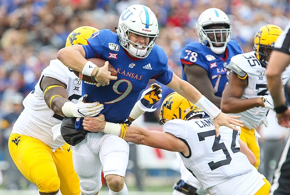 Kansas quarterback Carter Stanley (9) is corralled by the West Virginia defense on a run during the third quarter on Saturday, Sept. 21, 2019 at David Booth Kansas Memorial Stadium.