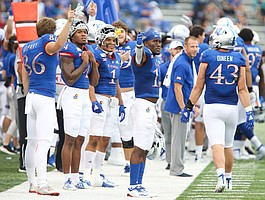 The Kansas bench signal the ball going their way after a recovered onside kick during the third quarter on Saturday, Sept. 21, 2019 at David Booth Kansas Memorial Stadium. Interference was called on the play and the ball was awarded to West Virginia.