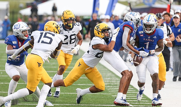 On the final play of the game, Kansas wide receiver Andrew Parchment (4) is shoved out of bounds along with Kansas running back Pooka Williams Jr. (1) by West Virginia safety Jake Long (22) on Saturday, Sept. 21, 2019 at David Booth Kansas Memorial Stadium.