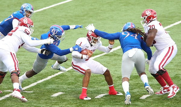 Kansas linebacker Azur Kamara (5) and Kansas defensive end Codey Cole III (94) try to wrap up Oklahoma quarterback Jalen Hurts (1) during the second quarter on Saturday, Oct. 5, 2019 at Memorial Stadium.