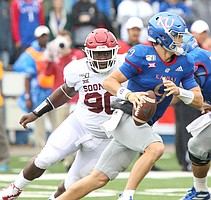 Kansas quarterback Carter Stanley (9) looks to throw as Oklahoma defensive lineman Neville Gallimore (90) closes in during the third quarter on Saturday, Oct. 5, 2019 at Memorial Stadium.