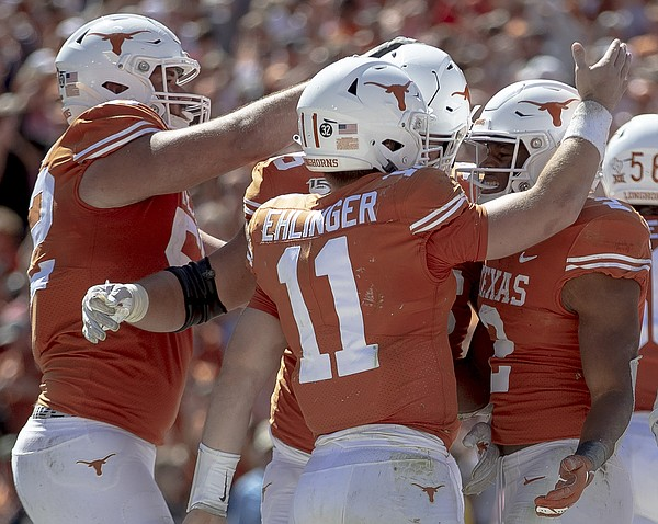 Texas quarterback Sam Ehlinger (11) celebrates a touchdown scored by running back Roschon Johnson (2) against Oklahoma during an NCAA college football game at the Cotton Bowl on Saturday, Oct. 12, 2019, in Dallas, Texas. (Nick Wagner/Austin American-Statesman via AP)